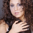 Stock Photo: Curly brunette girl with a black cat