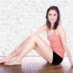 Brunette girl sitting on a wooden mat — Stock Photo #28495249