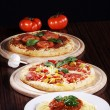 Two pizzas, pastand tomato on wooden table — Stock Photo #28495851