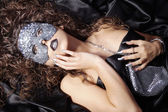Brunette curly girl in mask — Stockfoto