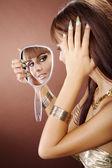 Oriental girl looking in the mirror — Stock Photo