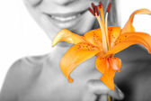 Girl in gray tone with orange flower — Stock Photo