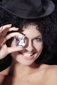Curly brunette girl in black hat with a diamond — Stock Photo