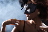 Curly brunette girl in a mask — Stok fotoğraf