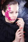 Chica morena con flores de color rosado en la cara — Foto de Stock