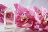 Pink orchid with massage oil — Stock Photo