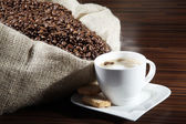 Coffee with sack of coffee beans — Stock Photo