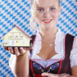Blonde girl holding a toy house — Stock Photo #28517267