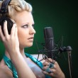 Blonde girl singing into a microphone — Stock Photo