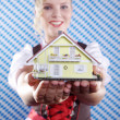 Blonde girl holding a toy house — Stock Photo