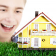 Boy with a model home on the grass — Stock Photo