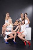 Vijf meisjes zitten op een zwart-witprinter catwalk — Stockfoto