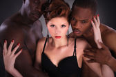Brunette girl with two African men — Stock Photo