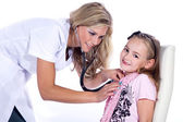 Cute girl being examine by pediatrician with stethoscope — Stock Photo