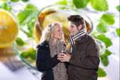 Couple in winter clothes on a background of tea — Stock Photo