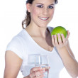 Brunette girl eating an apple and drinking water — Stock Photo #28520663