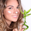 Beautiful woman using a skin care product — ストック写真
