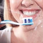 Closeup portrait of beautiful young woman brushing her teeth — Stock Photo #28523443