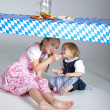 Two sisters under the table with food — Stock Photo