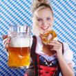 Happy woman in dirndl dloth holding Oktoberfest beer stein and pretzel in hands — Stock Photo #28523819
