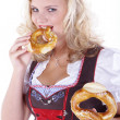 Young attractive woman bites in Oktoberfest Pretzel — Stock Photo