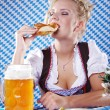 Happy woman in dirndl dloth holding Oktoberfest beer stein and pretzel in hands — Stock Photo #28523873