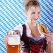 Happy woman in dirndl dloth holding Oktoberfest beer stein and pretzel in hands — Stock Photo #28523889