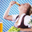 Happy woman in dirndl dloth holding Oktoberfest beer stein and pretzel in hands — Stock Photo #28523895