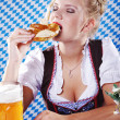Happy woman in dirndl dloth holding Oktoberfest beer stein and pretzel in hands — Stock Photo #28523915