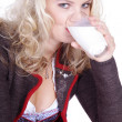 Girl in traditional dress drinking milk — Stock Photo #28523921