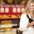 Blonde girl with bottle of wine — Stock Photo #28527207