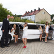 Five girls and a man near the limousine — Stock Photo