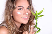 Beautiful woman using a skin care product — Stock Photo