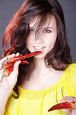Beautiful female eat chilli pepper — Stock Photo