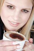 Blond girl drinking cappuccino — Stock Photo