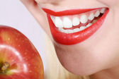 Beautiful female mouth with white teeth eating apple — Stock Photo