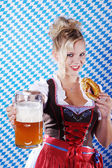 Happy woman in dirndl dloth holding Oktoberfest beer stein and pretzel in hands — Stock Photo