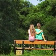 Young couple sitting on a bench — Stock Photo