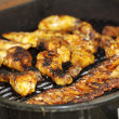 Chicken legs and ribs on the grill, across — Stock Photo