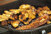 Chicken legs and ribs on the grill, across — 图库照片