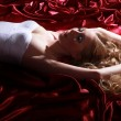 Blonde girl lying on the bed — Stock Photo