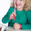 Little girl with a toothbrush and sweet food — Stock Photo