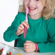 Stock Photo: Little girl with toothbrush and sweet food