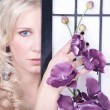 Girl with orchids behind the screen — Stock Photo