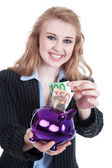 Woman with piggy bank smiling friendly — Stockfoto