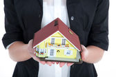 Businesswoman holding miniature house — Stock Photo