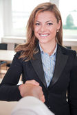 Businesswoman shakes hands with companion — Stock Photo