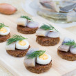Small canapes with herring, eggs and shallot — Stock Photo