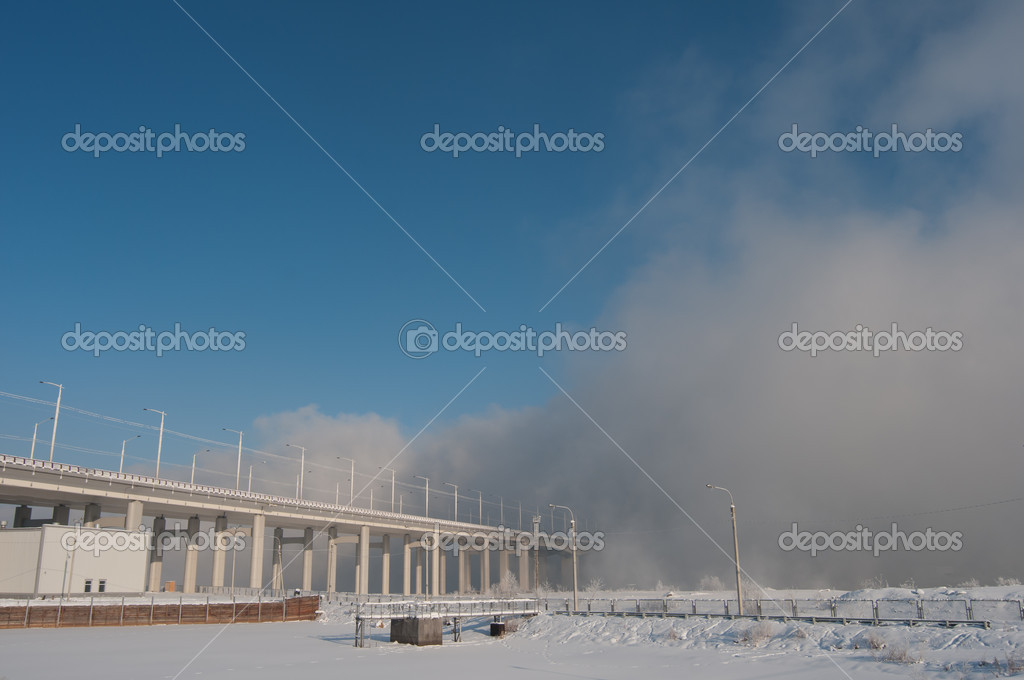 Bridge stretching into the fog. Frosty winter morning at the Siberian river. Severe frost mist created from the river. The sun illuminates the field of snow and bushes.Siberian winter very cold and frosty. Nature frozen in anticipation of spring.  — Stockfoto #17883513