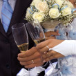 Bride and groom holding hands at wedding glasses — Stock Photo #18988511